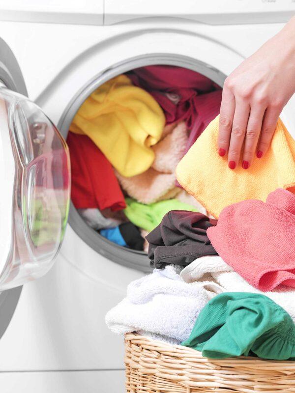 weibliche Hand belädt Waschmaschine